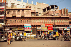 Sunny day on the street with rushing people and rickshaw taxi Royalty Free Stock Images