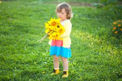 Happy child with bouquet of beautiful sunflowers. Sunny day, summer vacation. Cute little girl with yellow sunflowers, outdoor portrait royalty free stock photo