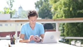 Sunny Day, usando Smartphone mientras que se sienta al aire libre en el trabajo metrajes