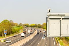 Sunny day view of UK motorway traffic with CCTV camera on foreground.  royalty free stock images