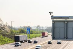 Sunny day view of UK motorway traffic with CCTV camera on foreground.  royalty free stock photos