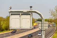Sunny day view of UK motorway traffic with CCTV camera on foreground.  royalty free stock image