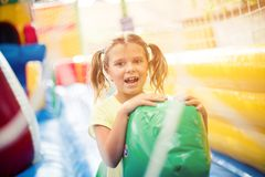 Sunny day was created for fun. Cheerful little girl playing alone in playground. space for copy. Close up stock images