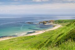 A sunny day at White Park Bay in county Antrim, Northern Ireland. Showing green hills sloping down to the sea shore, the white sandy beach and volcanic rocks stock photography