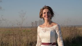 On a sunny day, a woman walks across a field in a white dress against a background of nature. stock footage