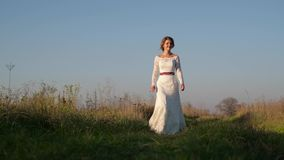 On a sunny day, a woman walks across a field in a white dress against a background of nature. stock video