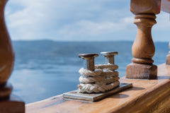 Sunny day on a yacht. A sea view from yacht. A bitt and a rope in the foreground , with wooden banisters around and blue sea  in the background. Sunny day Stock Photo