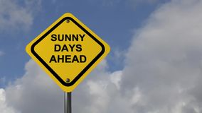 Sunny days ahead. Video with text 'sunny days ahead' in black uppercase letters on yellow diamond shaped board with moving clouds behind, suggestion of climate stock video footage