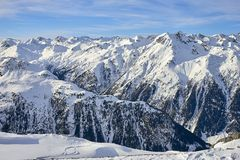 Sunny December day in Silvretta Alps - winter view on snow covered mountain slopes and blue sky Austria. Sunny December day in Silvretta Alps - winter view on Royalty Free Stock Photography