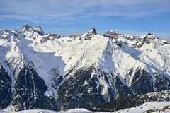 Sunny December day in Silvretta Alps - winter view on snow covered mountain slopes and blue sky Austria. royalty free stock photo