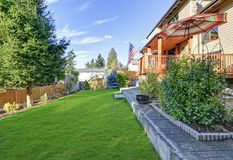 Sunny deck overlooking manicured backyard. Royalty Free Stock Photos