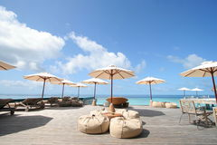 Sunny Deck with Umbrellas. Sunny Deck at tropical resort with umbrellas and wood chairs Royalty Free Stock Image