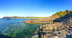 Sunny early on Giant Causeway. Giant Causeway sunny early when sun shines beautiful rocks, distance boats still moored to welcome sunny day, it's great to see royalty free stock photo