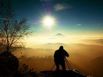 Sunny early winter  morning. Photographer preparing camera on tripod. Royalty Free Stock Photo