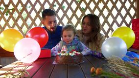 Sunny family celebrating their child is birthday. The girl blows out the candle stock footage