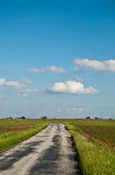 Sunny Farm Road. A small paved road leads through nicely manicured fields with farms in the background Royalty Free Stock Photography