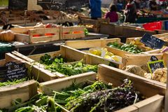 Sunny farmers market with vegetables on display in crates. Crates of vegetables out for sale at a farmers market in Rennes, France in open air setting royalty free stock photos