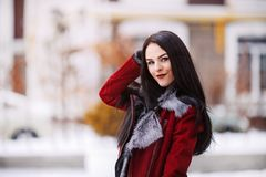 Sunny frozen morning of fashionable young woman smiling on winter street full of snow Stock Photos