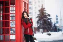 Sunny frozen morning of fashionable young woman smiling on winter street full of snow Stock Image