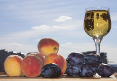 Sunny fruits and wine. Peaches and plums with wine. Sunny day Stock Photo