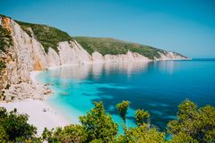 Sunny Fteri beach lagoon with rocky coastline, Kefalonia, Greece. Tourists under umbrella chill relax near clear blue stock photo