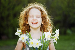 Sunny girl with a flower in her hand. Mothers day concept. Royalty Free Stock Photography