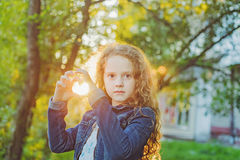 Sunny girl folded her hands a heart shaped. Curly girl folded her hands a heart shaped Royalty Free Stock Images