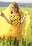 Sunny girl in a summer dress with polka dots nestled bright yell Royalty Free Stock Photo