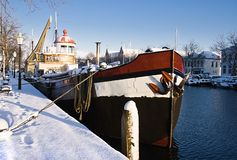 Sunny harbour with iron ship in winter snow Royalty Free Stock Photo