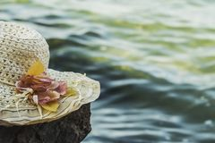 Sunny hat with flowers lies on a rock in front of the sea, toned. stock photos