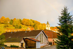 Sunny hill crossed the pale rainbow. A pale rainbow over the sunny  mountain autumnal french village Stock Photos