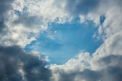 Sunny hole in dark cloudy sky Royalty Free Stock Images