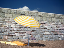 Sunny holiday. Yellow sunshade on the beach stock images