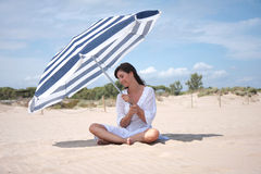 Sunny holiday. Woman sunbathing in the sand on the sea royalty free stock image