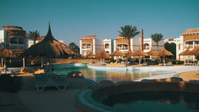 Sunny Hotel Resort with Blue Pool, Palm Trees and Sunbeds in Egypt. Sunny Hotel Resort with luxury blue swimming pool, palm trees, Beach Umbrellas and sunbeds in stock footage