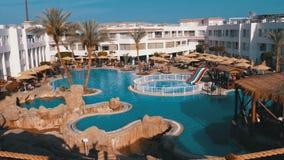 Sunny Hotel Resort con la piscina, gli ombrelli di spiaggia ed i lettini blu di lusso nell'Egitto stock footage