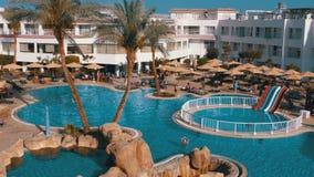 Sunny Hotel Resort con la piscina, gli ombrelli di spiaggia ed i lettini blu di lusso nell'Egitto video d archivio