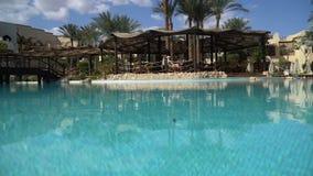 Sunny Hotel Resort con la piscina, i Waterslides, le palme, gli ombrelli di spiaggia ed i lettini blu di lusso nell'Egitto ricco archivi video