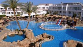 Sunny Hotel Resort met Luxe Blauw Zwembad, Strandparaplu's en Sunbeds in Egypte stock videobeelden