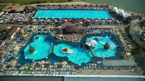Sunny Hotel swimming pool - crowd of people rest and swim in resort, top view, time-lapse. Wide angle stock video