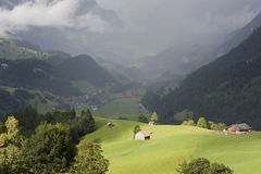 A house on a sunlit hill in front of clouds in Switzerland Royalty Free Stock Photos