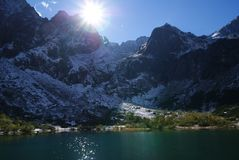 Sunny and icy mountain with lake. stock photography