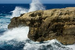 Malta, Gozo island coastline, wild waves and rocks, blue sky - sea horizon Stock Image