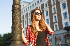 Sunny lifestyle fashion portrait of young stylish hipster woman walking on the street, wearing trendy outfit and hat. Royalty Free Stock Images