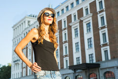 Sunny lifestyle fashion portrait of young stylish hipster woman walking on the street, wearing trendy outfit and hat. Stock Images