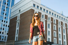 Sunny lifestyle fashion portrait of young stylish hipster woman walking on the street, wearing trendy outfit and hat. Royalty Free Stock Photography
