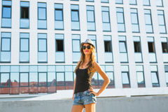Sunny lifestyle fashion portrait of young stylish hipster woman walking on the street, wearing trendy outfit and hat. Stock Photos