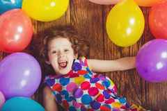 Sunny little girl in birthday party lying on wooden floor  Royalty Free Stock Photo