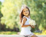 Sunny little girl with a bouquet of chamomiles flowers in spring. Day stock photo
