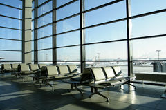 Sunny lounge in airport with no people. At winter time with aircraft standing behind the window Stock Photos